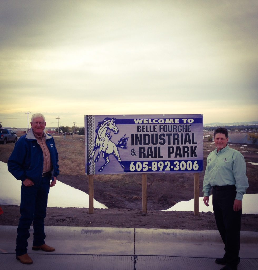 Belle Fourche, S.D., Mayor Gary Hendrickson and then-interim economic development director Jim Doolittle pose in front of their community's investment into a multi-million-dollar industrial rail park. Belle Fourche currently sees more traffic on Highway 85 than there is on I-90