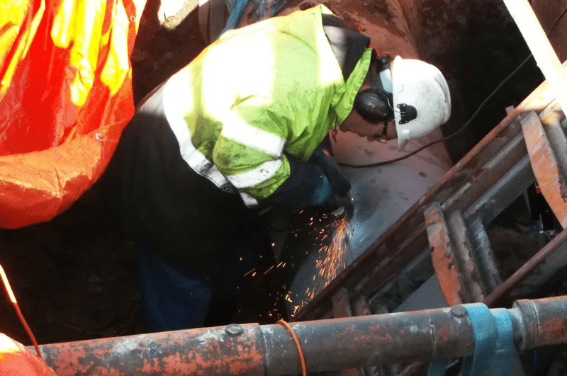 Technicians remove the crack in the seam weld with a grinder to prepare the surface of a carbon steel crude oil pipeline for a composite repair. Photos courtesy of CSNRI