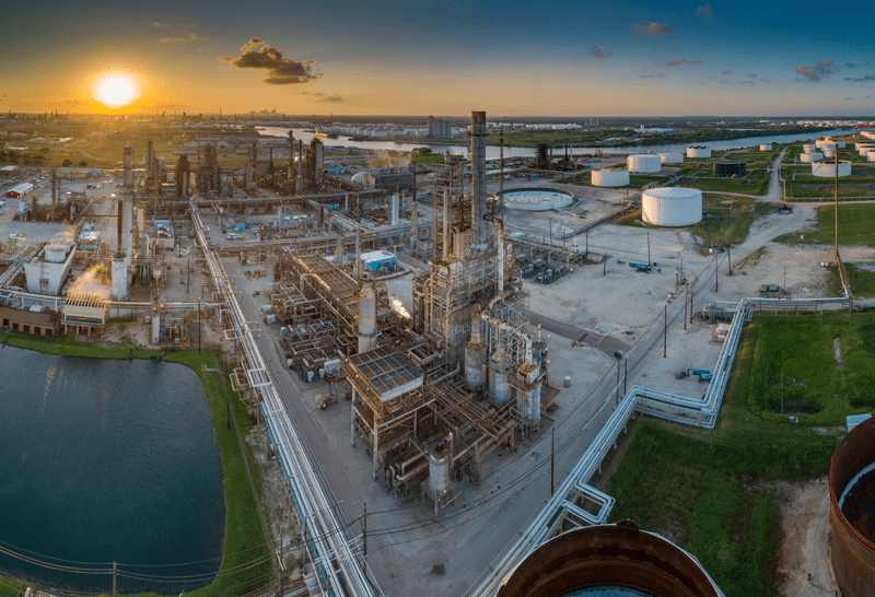 The sun sets over this Houston ship channel refinery and tank field. A panoramic photo taken from the air.
