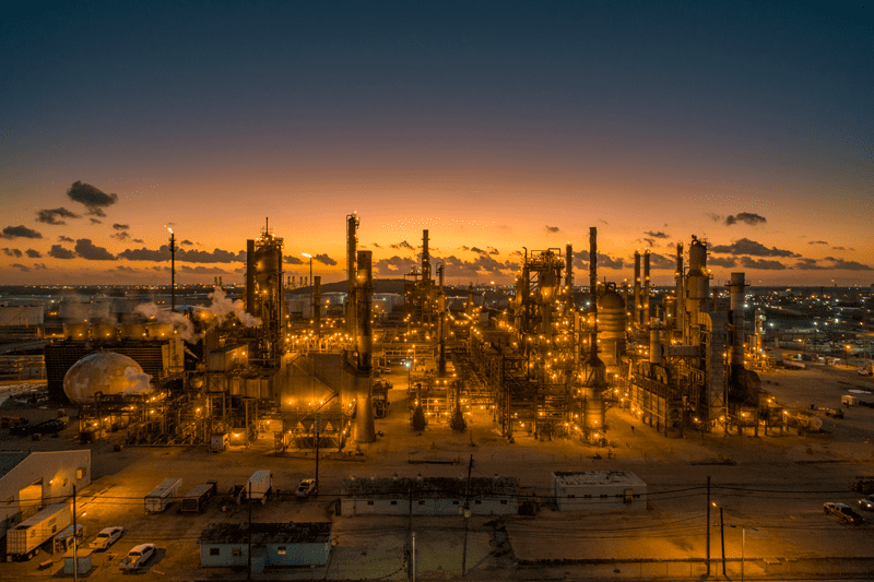 Moments before sunrise the refinery is lit up like the golden hues behind it. An aerial shot taken by drone.